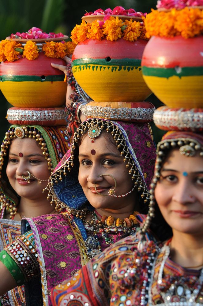 Women smiling with pots on their heads