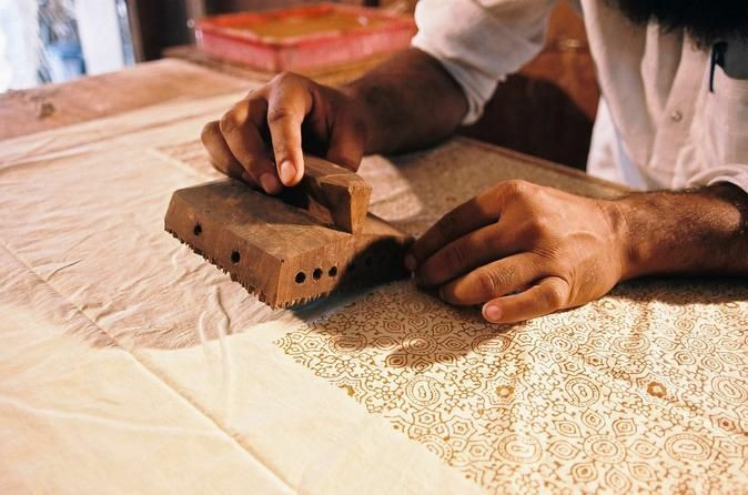 An artist printing using Anokhi blocks by hand
